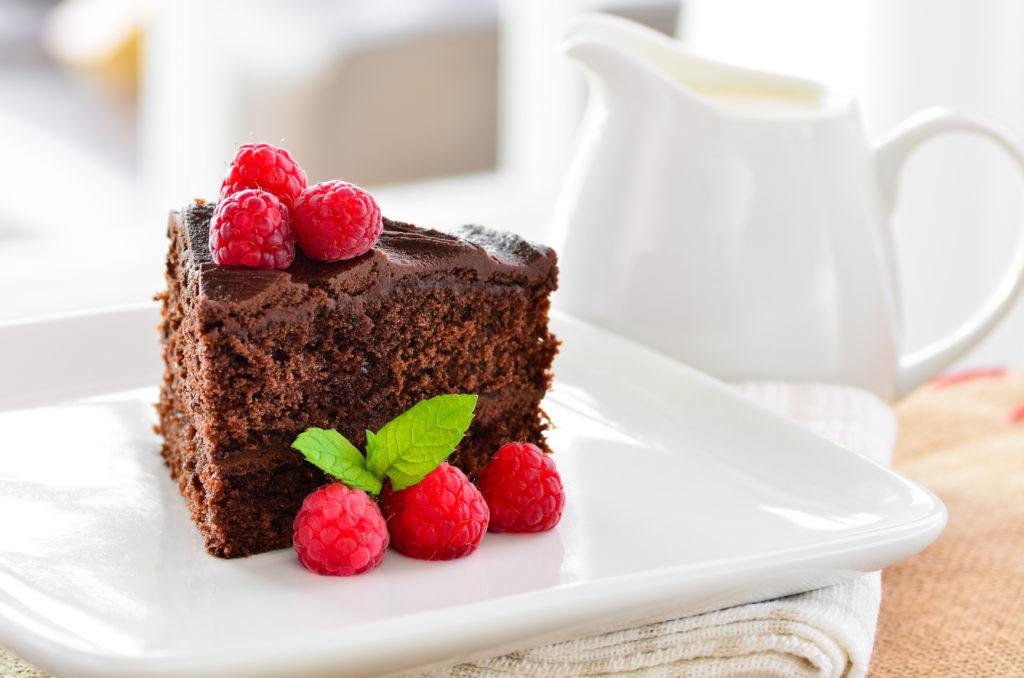Fresh home made sticky chocolate fudge cake with raspberries